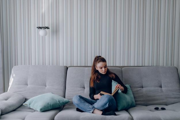 nastolatka czytająca książkę na kanapie